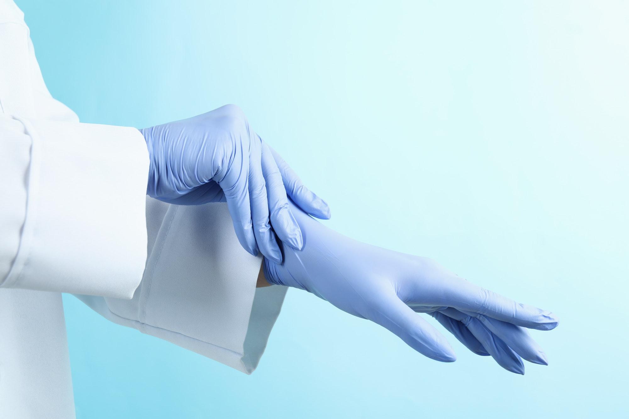 Doctor putting medical gloves on blue background